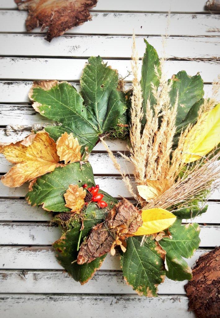 Aus großen  Blättern, Moos,  Rinde, Gräser, Hagebutten und Vogelbeeren wird ganz schnell ein herbstliche Kranz. Dafür benötigt man nur einen alten Kranz und etwas Draht.  Alles auflegen und nach und nach mit dem Draht umwickeln.