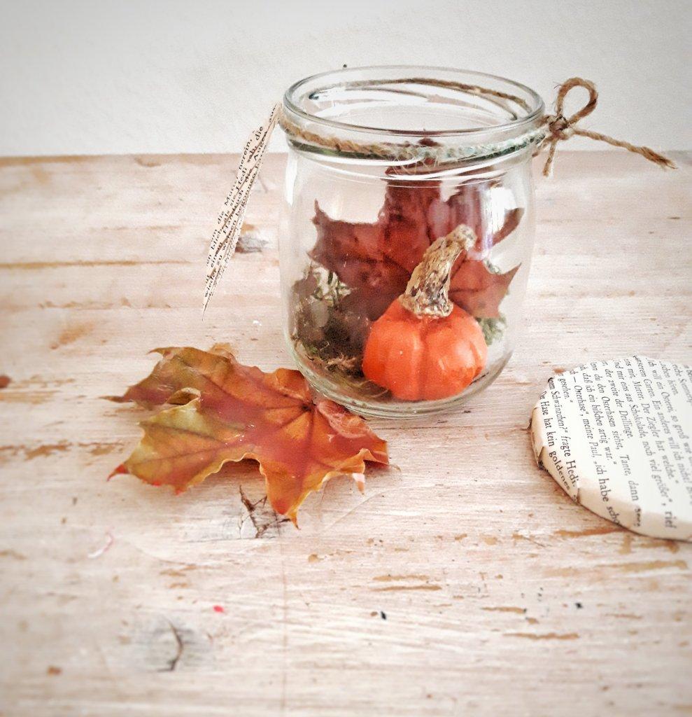 Aus Einmachglas, einer Buchseite, Kürbis und Blätter wird eine tolle Upcycling-DIY-Idee
