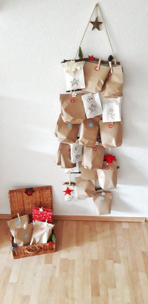 An einer selbstgebastelten Strickleiter aus Stöckern aus dem Wald werden dieses Jahr die Adventstütchen aufgehängt. Der Strohkoffer ist aus dem Bestand der Oma. Nachhaltig und dekorativ. Ein echtes Upcycling Highlight. DIY Idee Adventskalender.